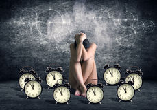 Time goes by. Nude woman sitting head in hands among a large number of watches and alarm clocks Stock Images