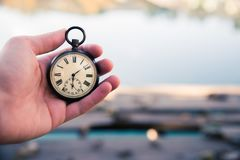Time goes by: vintage watch outdoors, hand-held; wood and leaves. Hand held stop watch outdoors, autumn, blurry background time goes clock duration vintage speed stock image