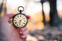 Time goes by: vintage watch outdoors, hand-held; wood and leaves. Hand held stop watch outdoors, autumn, blurry background time goes clock duration vintage speed stock images