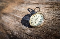 Time goes by: vintage watch outdoors; wood and leaves. Vintage watch lies on a wood board, autumn time goes clock duration speed up period leisure velocity royalty free stock photo