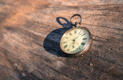 Time goes by: vintage watch outdoors; wood and leaves. Vintage watch lies on a wood board, autumn time goes clock duration speed up period leisure velocity royalty free stock photography