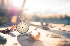 Time goes by: vintage watch outdoors; wood and leaves. Vintage pocket watch on a wood board, colourful leaves, autumn, sunshine time goes clock duration speed up royalty free stock photography