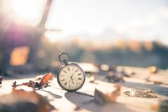 Time goes by: vintage watch outdoors; wood and leaves. Vintage pocket watch on a wood board, colourful leaves, autumn, sunshine time goes clock duration speed up royalty free stock photos