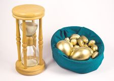 Time is gold. Sand clock and golden nuts and eggs royalty free stock images