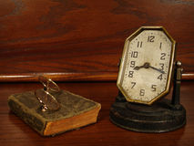 Time Gone Past. Antique clock, book and glasses on wooden desk or nightstand Stock Image