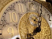 Time on a grandfather clock. 's gold face Stock Image