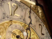Time on a grandfather clock. 's gold face Royalty Free Stock Photo
