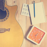 Time for Guitar song writing with a red clock. Time for Guitar song writing with a red clock in vintage tone Royalty Free Stock Photo
