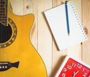 Time for Guitar song writing with a red clock. Time for Guitar song writing with a red clock on wooden floor Royalty Free Stock Photography