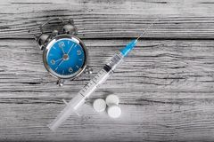 Time heals concept. Alarm clock with pills and syringe on wooden background stock photos