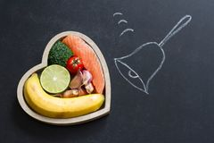 Time for health heart abstract diet food concept on blackboard with bell Royalty Free Stock Image