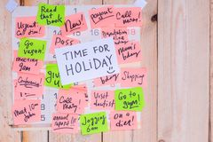 Time For Holiday written on paper note on a wall calendar full of pink and green notes with wooden background and copy space royalty free stock photography