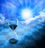 Time Hourglass Background Sun Sky. A conceptual image of an hourglass space and time Stock Photo