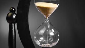 Time, the hourglass turns the hand and begins the countdown of five minutes in black and white shades. HD stock video footage