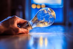 Time for ideas, inspiration and invention: Hands are holding a LED lightbulb. Hands are holding a LED lightbulb over the wooden floor. Symbol for ideas and stock images