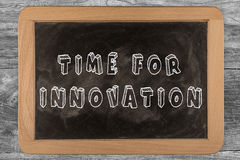 Time for innovation chalkboard with outlined text. On wood Stock Image