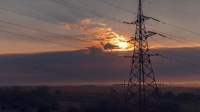 Time interval. Sunrise on the background of power lines. A delightful sunrise in the steppe and among the fields, against the backdrop of high-voltage power stock footage