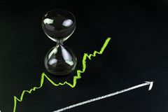 Time for invest or long term investment concept, hourglass or sandglass with black sand inside on stock market green line rising. Chart drawing with chalk on stock photo