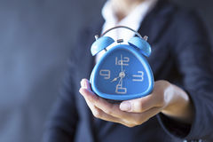 Time keeper. Business girl holding clock stock photography