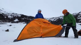 Time laps as two travelers set up a tent in the mountains in the snow.