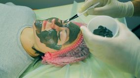 Time laps. Hands of the man of the cosmetician put on the face of the woman a liquid black mask. Close-up stock video footage