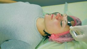 Time laps. Hands of the man of the cosmetician put on the face of the woman a liquid black mask. Close-up stock footage