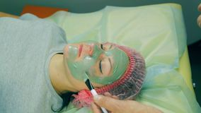 Time laps. Hands of the man of the cosmetician put on the face of the woman a liquid green mask with the help of a brush. Close-up stock video footage