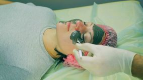 Time laps. Hands of the man of the cosmetician put on the face of the woman a liquid mask. Close-up stock video footage