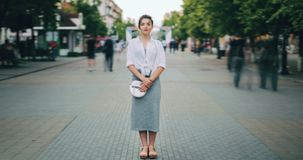Time lapse of attractive adult woman standing in city center in busy street. Looking at camera wearing casual clothes while crowds of people are walking by stock video