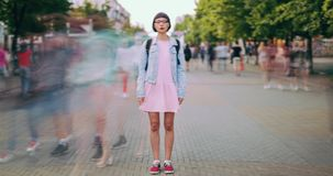 Time lapse of attractive teenage girl standing in city center in busy street. Looking at camera wearing trendy clothes while crowds of people are walking by stock footage