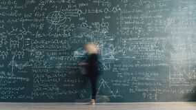 Time lapse back view of smart lady scientist writing formulas on chalkboard