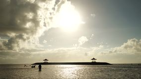 Time lapse of beautiful view in Sanur beach. Time lapse of beautiful landscape in Sanur beach with moving clouds and silhouette of people playing on the beach stock video