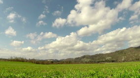Time lapse of blue sky over green field stock video footage