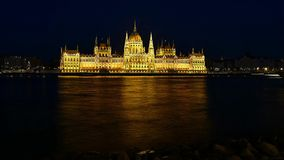 Time lapse of Budapest National Parliament illuminated at night. Danube river in foreground stock video