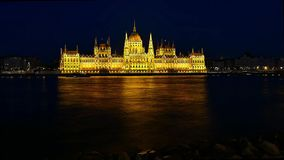 Time lapse of Budapest National Parliament illuminated at night. Danube river in foreground stock video footage
