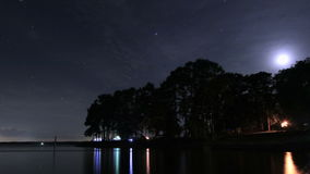 Time Lapse of Camping by Lake at Night Under the Trees stock video footage