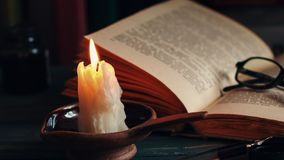 Time lapse candle and old books at night time. Close up view. Cinematic color grading stock footage