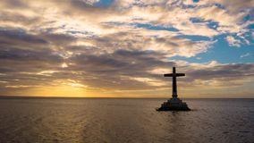 Timelapse: Sunken Cemetery cross in Camiguin island, Philippines. Time lapse: Catholic cross in sunken cemetery in the sea at sunset, aerial view. Colorful stock video