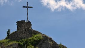 Time lapse - Christian cross erected on a rock against cloudy sky. stock video footage