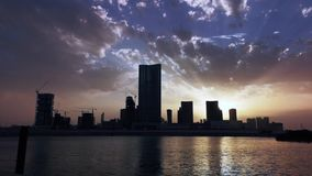 Time lapse of city skyline and work district with modern skyscrapers at sunset - Al Reem Abu Dhabi.  stock footage