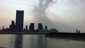 Time lapse of city skyscrapers in front of a lake at sunset - Al Reem Abu Dhabi.  stock video