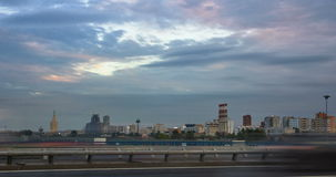 Time lapse cityscape at sunset with the movement of clouds and various buildings at background and automobile traffic on a highway. Timelapse cityscape at sunset stock footage