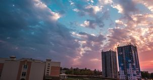 Time lapse clip of evening fluffy curly rolling clouds of awesome sunset against the background of multi-storey apartment building stock footage