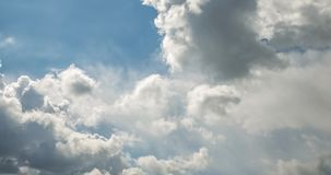 Time lapse clip of gray fluffy curly rolling clouds before storm in windy weather with sun rays stock footage