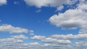 Time-lapse clip of white fluffy clouds over blue sky on sunny day.  stock footage