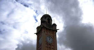 Time-lapse of clock tower with moody clouds stock video footage