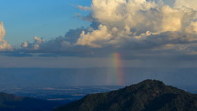Time-lapse of cloud with rain and rainbow over mountain at Khao Kho, Phetchabun, Thailand