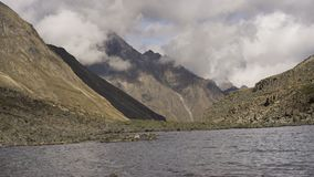 Time lapse. Clouds in the mountains are moving against the backdrop of high rocky peaks. View of a mountain lake, Kodar ridge, Russia stock video