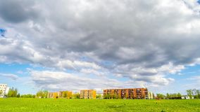 Time lapse. Clouds over the green field in city. stock footage