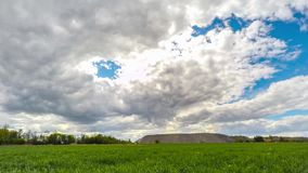 Time Lapse clouds over the green field. stock video footage
